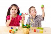 Two kids paint easter eggs