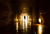 stock photo of tunnel  - silhouette of human in old brick tunnel light at end of tunnel - JPG