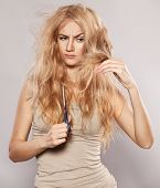 foto of split ends  - Young woman looking at split ends - JPG