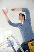 foto of precaution  - Electrician installing fire alarm inside house - JPG