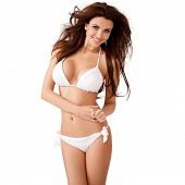 stock photo of swimsuit model  - Vivacious sexy young brunette woman with a beautiful smile and her hair blowing in the breeze posing in a white bikini  three quarter isolated studio portrait - JPG