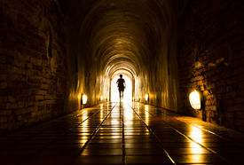 image of underworld  - silhouette of human in old brick tunnel light at end of tunnel - JPG
