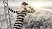 stock photo of spyglass  - woman stands on top of a ladder using a spyglass - JPG