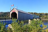 foto of covered bridge  - Wooden covered Bridge in New Brunswick Canada with colorful Autumn trees in the background - JPG