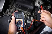 stock photo of grease  - Auto mechanic working in garage - JPG