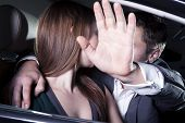 stock photo of hand kiss  - Young couple kissing in car and man is shielding with his arm - JPG