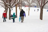 stock photo of snowy hill  - Family walking to the sledding hill - JPG