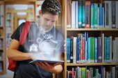 image of hologram  - Handsome college student working on his digital tablet with futuristic interface in university library - JPG