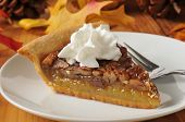 pic of pecan  - Pecan pie topped with whipped cream on a colorful holiday table - JPG
