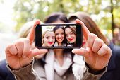 foto of selfie  - Students taking a self portrait with smart phone - JPG