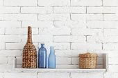 stock photo of bottles  - Decorative shelf on white brick wall with vintage bottles and wicker jars on it - JPG