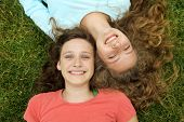 Smiling teenagers friends lying on a grass in a park