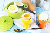 stock photo of continental food  - Boiled eggs in pan and eggcup on color wooden background - JPG