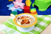 Bowl of porridge for baby and toys  on table, on toys background