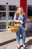 picture of vivacious  - Beautiful vivacious woman shopping for groceries standing in front of a supermarket with a basket of fresh fruit and vegetables over her arm - JPG