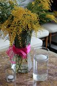 foto of centerpiece  - Pretty yellow buds of the yellow mimosa flower in a centerpiece arrangement of glass vase on table - JPG