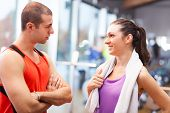 Personal trainer talking to a girl in a fitness club