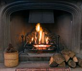 stock photo of cozy hearth  - A roaring fire within a large stone arched fireplace with pile of logs and basket of pine kernels in the foreground - JPG