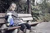 stock photo of bullying  - Little girl coming from school sitting lonely at a bench outdoors - JPG