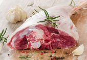 pic of lamb chops  - Raw lamb leg on a wooden table - JPG