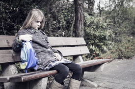 image of school bullying  - Little girl coming from school sitting lonely at a bench outdoors - JPG