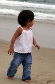 stock photo of children beach  - Child walking on beach watching waves - JPG