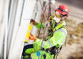 stock photo of measuring height  - Industrial climber measuring with level tube during winterization works - JPG