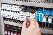 stock photo of electrician  - Cropped image of male electrician examining fusebox with screwdriver - JPG