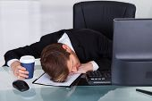 pic of contract  - Overworked businessman holding disposable coffee cup while resting on contract paper at office desk - JPG