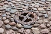 stock photo of manhole  - Old steel sewer manhole on the cobblestone road - JPG