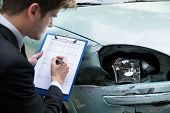 foto of clipboard  - Side view of writing on clipboard while insurance agent examining car after accident - JPG