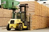 picture of lift truck  - Large lift truck moving a stack of green fir 2 x 4 lumber studs at a small log processing mill in southern Oregon ready for the drying kiln - JPG