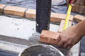 picture of bricklayer  - the worker is measuring the brick before bricklaying - JPG