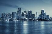 stock photo of reflection  - Miami skyline panorama at dusk with urban skyscrapers and bridge over sea with reflection - JPG