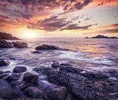 stock photo of karnataka  - Sea with rocks at violet sunset sky in Om beach Gokarna Karnataka India - JPG
