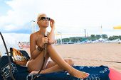 stock photo of hookah  - Woman with hookah on the beach in bikini - JPG