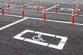 foto of physically handicapped  - White wheelchair icon on a gray asphalt parking lot - JPG