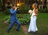 stock photo of flashing  - Professional wedding photographer takes a picture of the bride camera flash flashing - JPG
