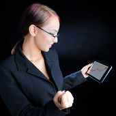 stock photo of ascending  - Attractive young business woman looking at an ascending graph on a tablet computer against a black background - JPG