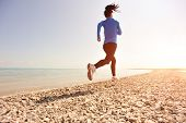 image of ponytail  - Runner athlete running on stone beach of qinghai lake - JPG