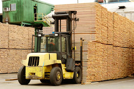 image of logging truck  - Large lift truck moving a stack of green fir 2 x 4 lumber studs at a small log processing mill in southern Oregon ready for the drying kiln - JPG