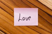 picture of office romance  - small pink note with the word love on an office desk background - JPG