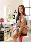 pic of pulling hair  - Attractive young casual woman sitting at home on chair hugging her pulled up leg - JPG