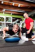 picture of personal trainer  - A shot of a male personal trainer assisting a male athlete doing push - JPG