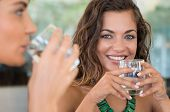 image of minerals  - Two Female Friends Drinking Mineral Water With Glass At Bar - JPG
