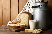 stock photo of milk products  - Retro can for milk with fresh bread and glass of milk on wooden background - JPG