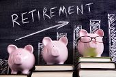 stock photo of retirement  - Three pink piggy banks standing on books next to a blackboard with retirement savings chart. Sharp focus on the piggy banks.