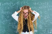 pic of nerd  - Crazy nerd blond student girl holding hair surprised expression in green chalk board - JPG