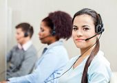 foto of telemarketing  - Portrait of confident female customer service representative with colleagues in background at office - JPG