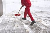 stock photo of snow shovel  - Worker in red uniform removes snow with red shovel - JPG